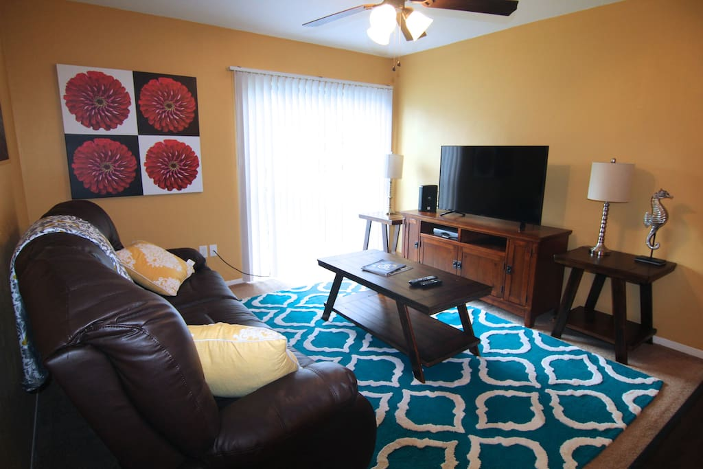 Comfortable living area with reclining leather couch and large TV.