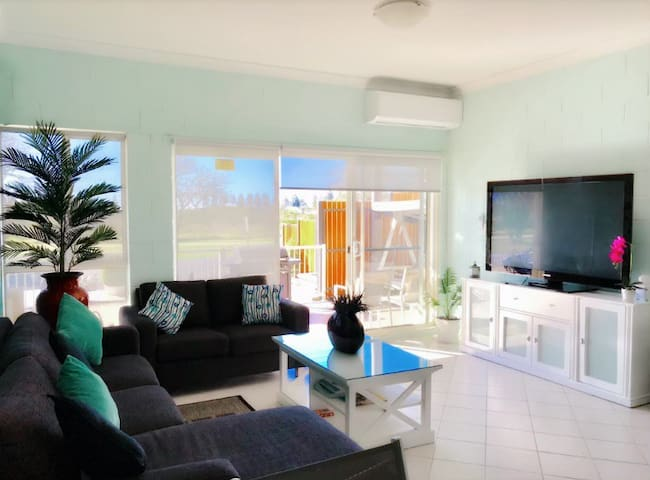"Spacious air-conditioned living room with 65"" TV."