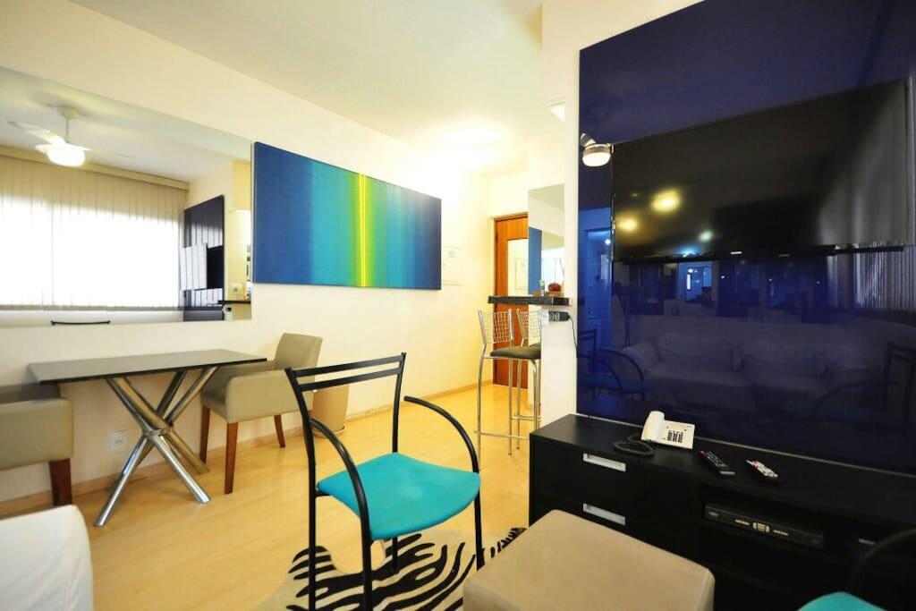 Espelhos na parede e tela azul e . Amarelo ,  onde tem Mesa d granito negro , e 2 poltronas cor castor em couro , painel de vidro c tv , e rack