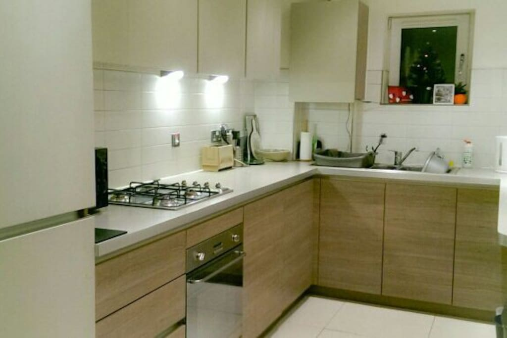 Modern kitchen with fridge freezer, washer/dryer, dishwasher, microwave, gas hob and electric fan oven
