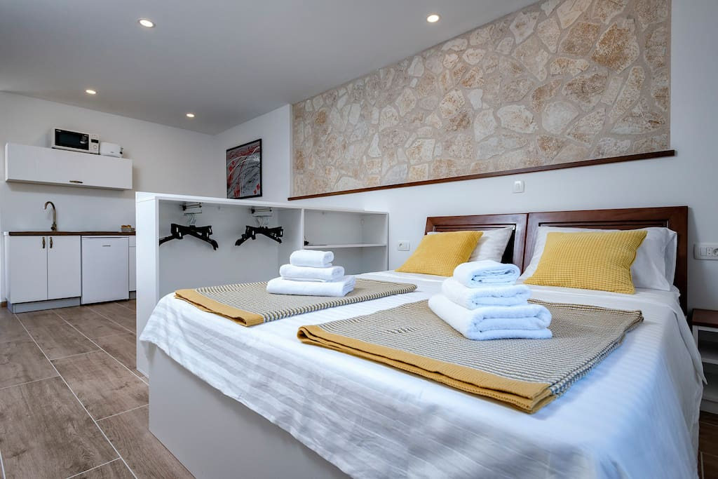 Double bed inside the old stone house, which keeps the temperature nice and cool. The room has A/C and satellite smart TV