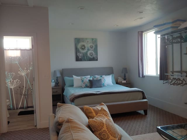Cute bedroom space with comfortable king-sized bed, open closet space, humidifier, alarm clock, and extra bedding/pillows.