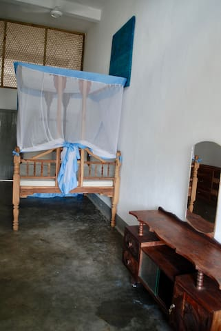 Light room with queen size Zanzibar-style bed (150x200 cm), mosquito net, fan, WIFI, table, 2 chest of drawers, mirror, hangers and window with amazing view!