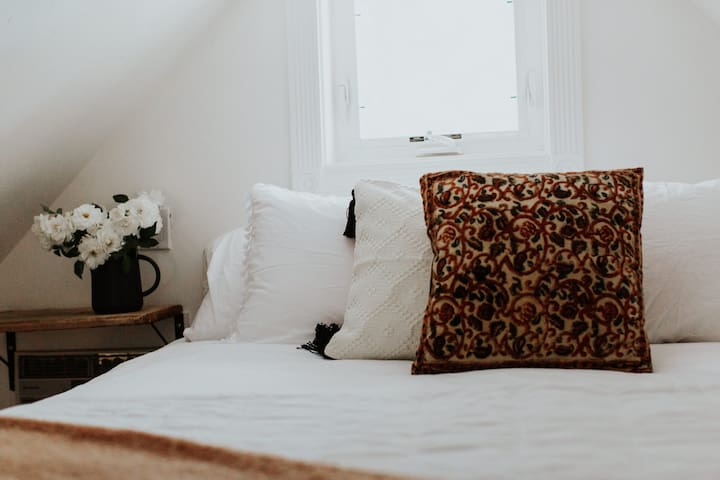 plush california king bed in a loft bedroom in upstairs of cottage