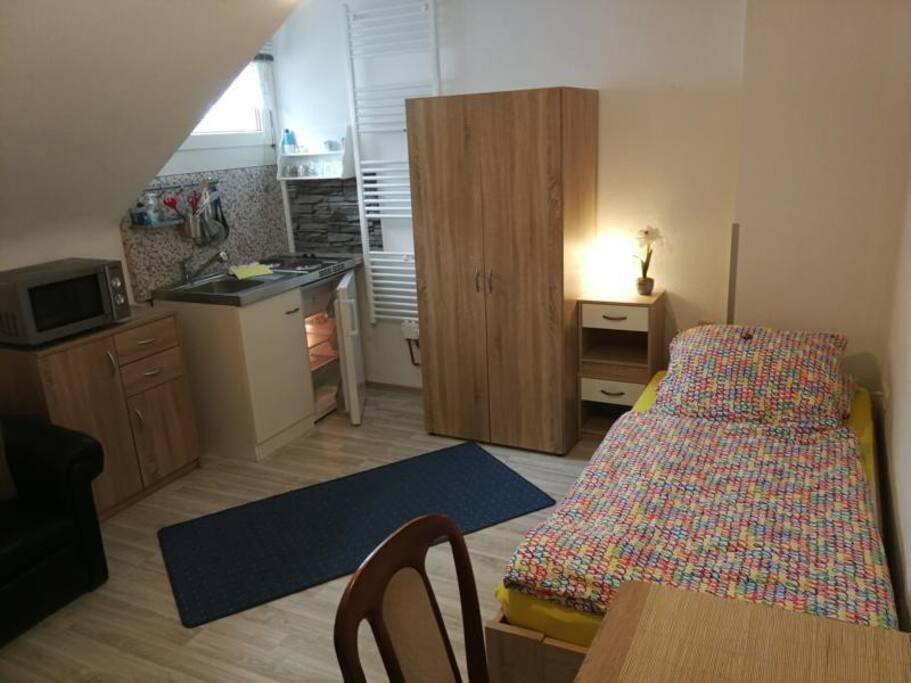Zimmer Moonlight im Überblick: mit Singleküche, Kühlschrank, Spüle, Mikrowelle auf Utensilienschrank, Bett, Schrank, Nachtschränkchen