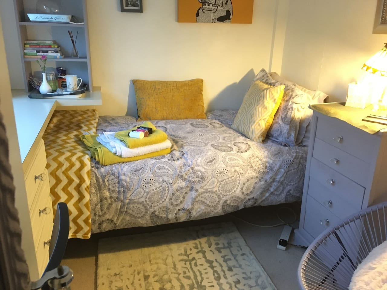 Bed drawers and chair in single room