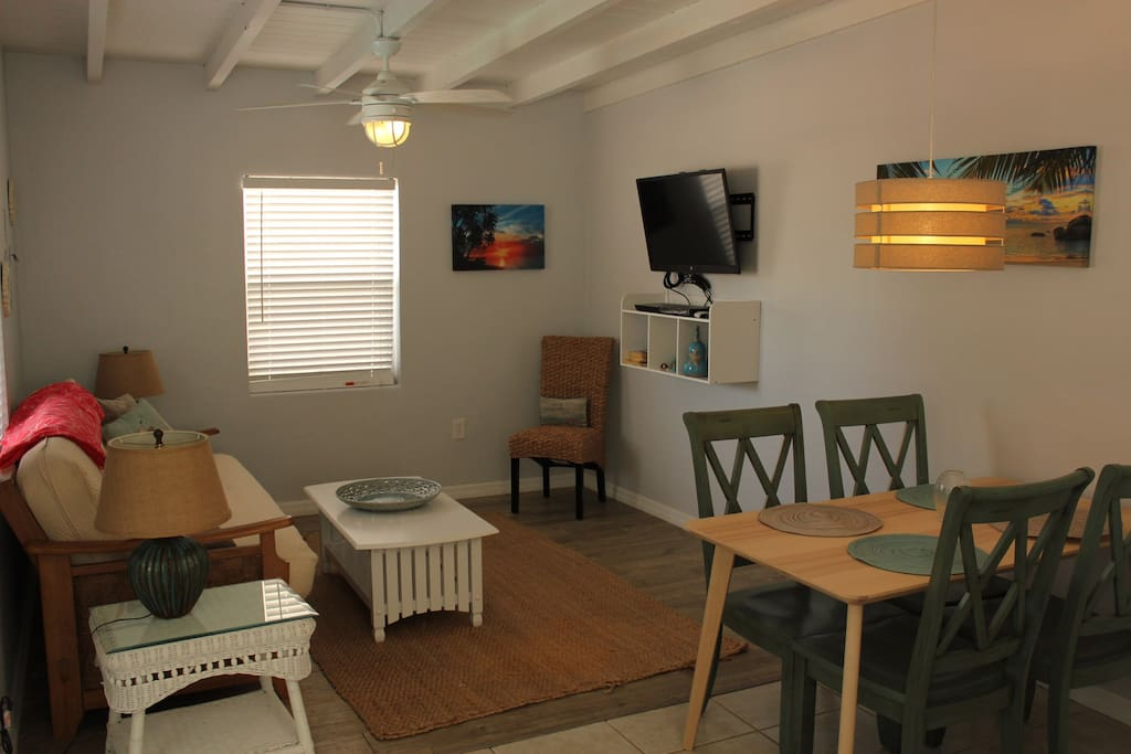 The living/dining area features a table for four and a futon with a comfort top