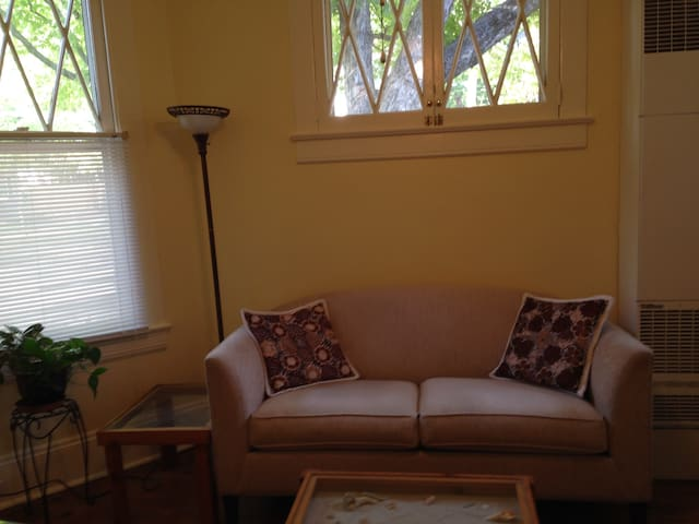 Living room has ceiling fan, digital cable tv, bookcase with books & games.