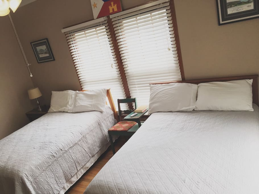 Two full beds, a desk, nightstands, and lamps