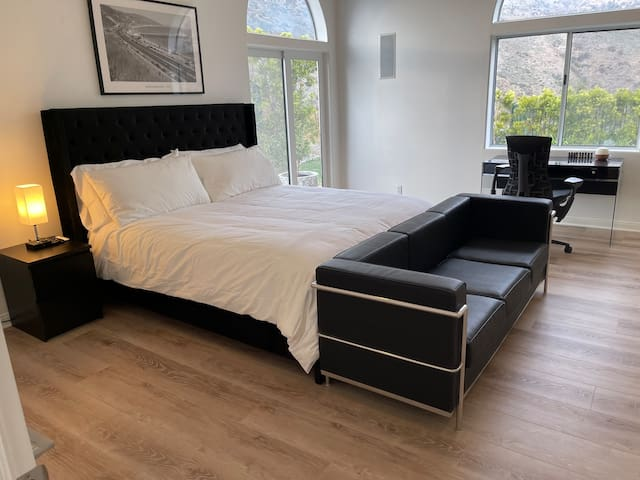 Master bedroom with California King bed. Gorgeous views of Santa Monica mountains through window and side window shows the Pacific Ocean