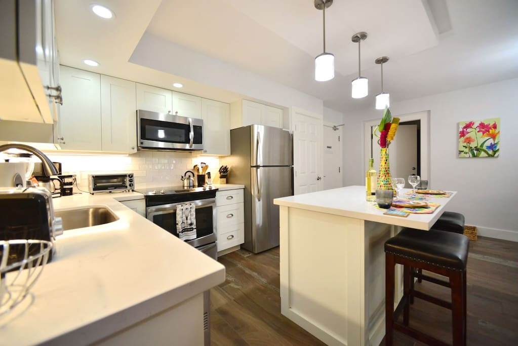Remodeled kitchen features full-size stainless steel appliances (including a dishwasher, which is a rarity in most vacation homes), tile backsplash, and modern lighting.