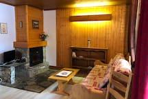Coin salon avec cheminée à insert Jotul et télé TNT satellite