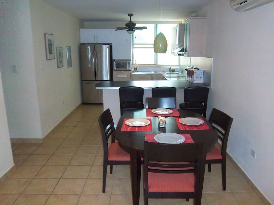 Fully equipped kitchen with stove and oven, microwave, blender, coffee maker, pots and pans.
