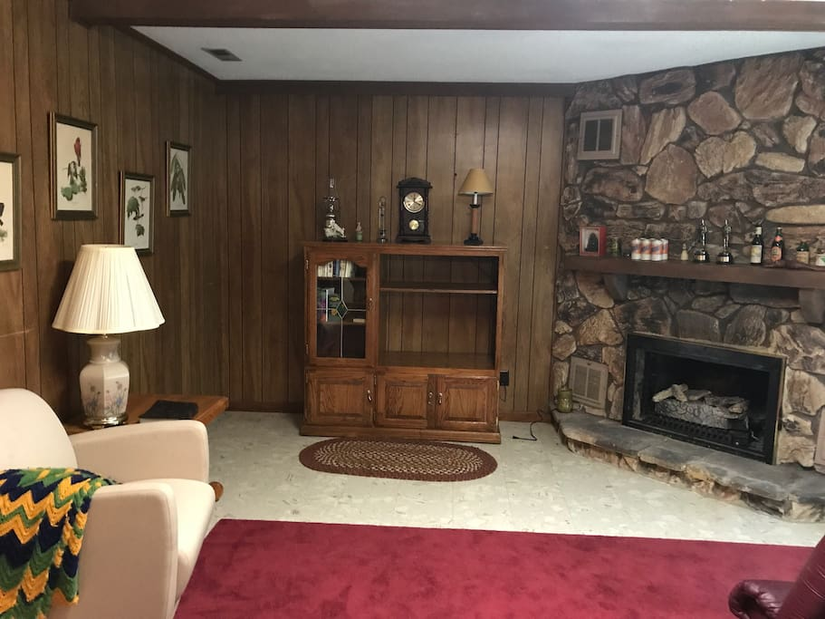 Living room with fireplace, exercise bike, couch & chair