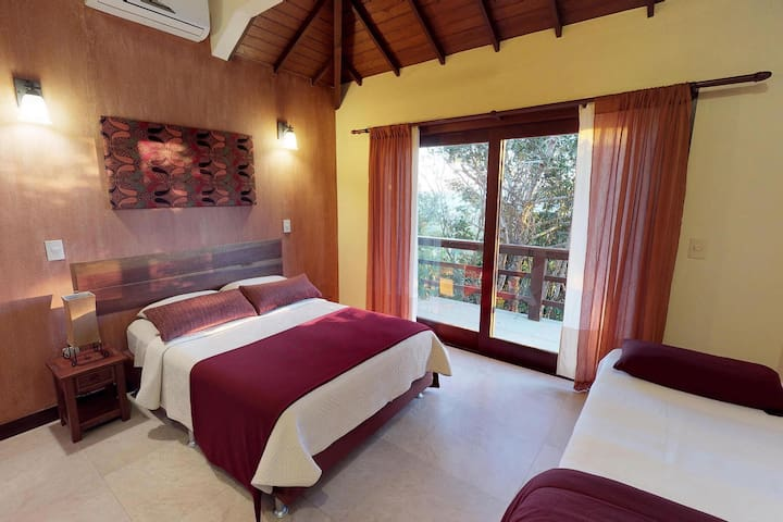 Our Pool view bedroom is a shared space  with a double bed and 2 single beds, air conditioner and ceiling fans with French doors that lead to the front balcony