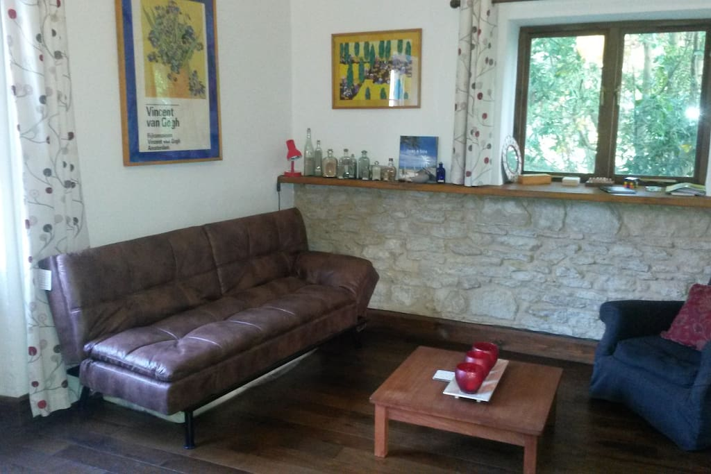 Lounge with original stone wall. Sofabed opens easily to accommodate extra guests. There's a memory foam topper for extra comfort. Size is 120cm x 190cm