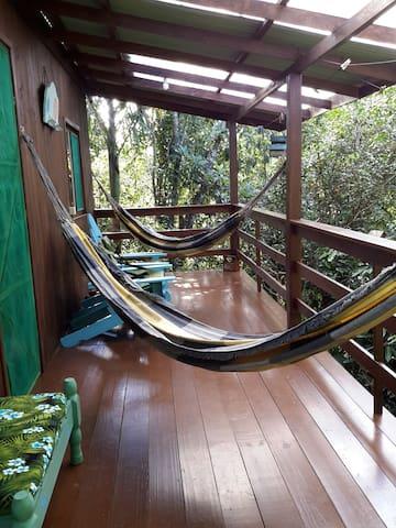 Varanda com cadeiras e redes para descanso
