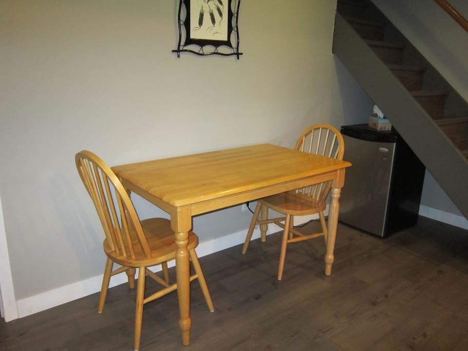 Extra table and chairs in basement with small fridge.