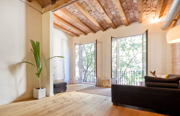 Living room with balcony and the view onto the tree lined street