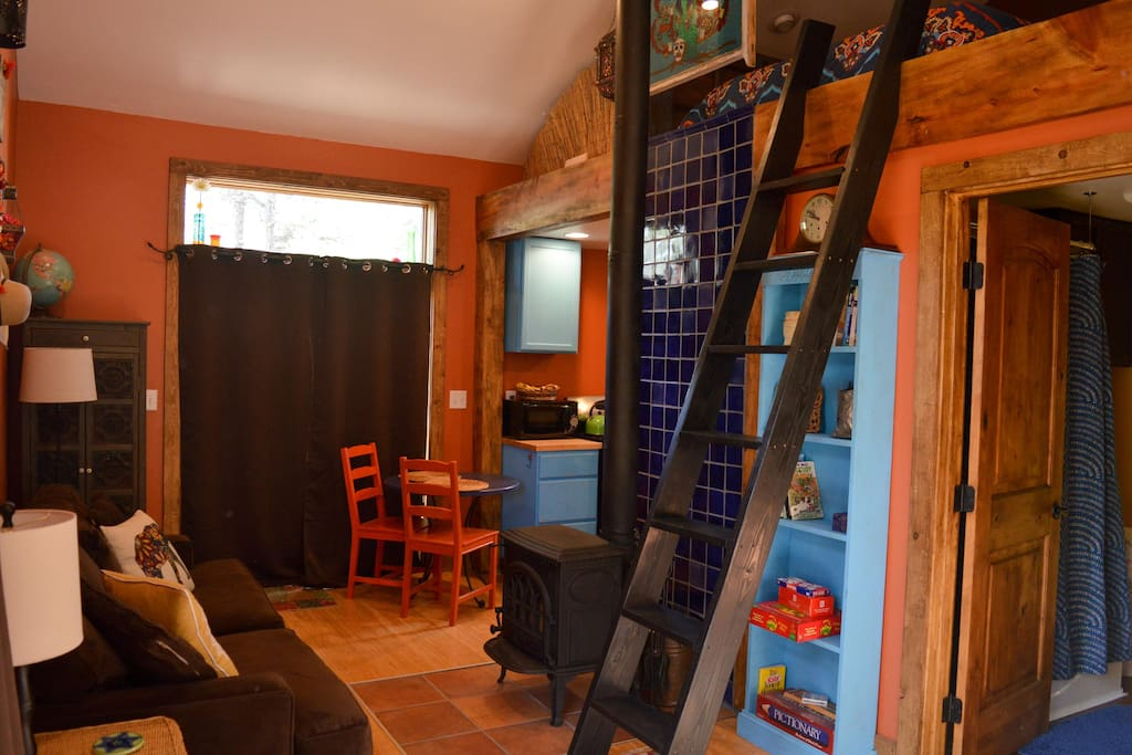 The casita has a comfy living room, well stocked bookshelf, kitchen, and sleeping loft.