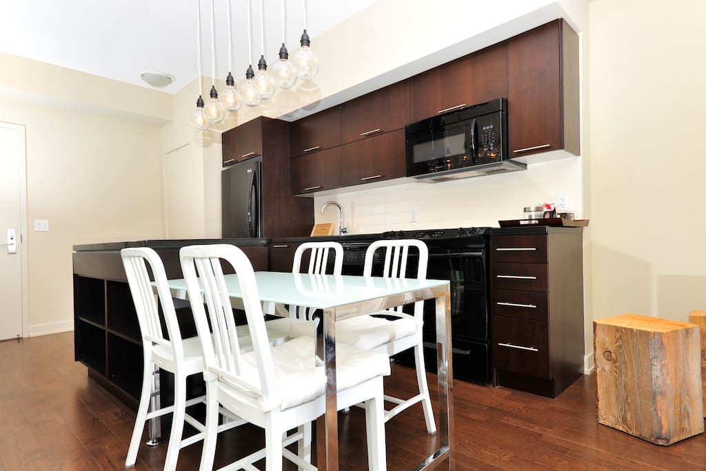 Custom made lights, designer furniture, plenty of cupboard space with dishes, pots, cutlery. Open storage on back of island can be used for shoes!