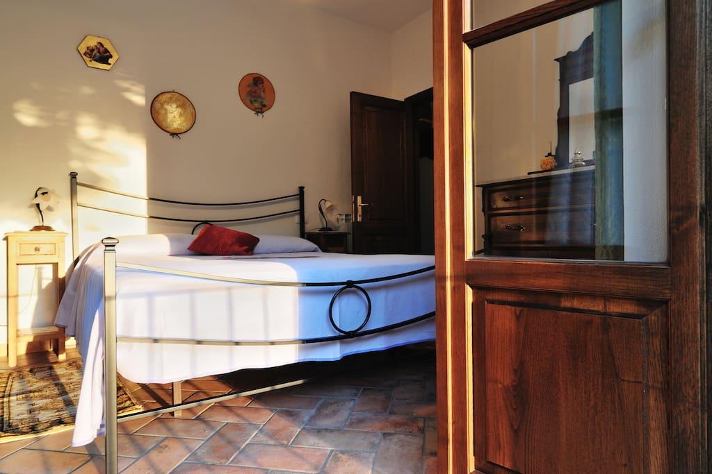 """camera """"Ottocento"""": letto matrimoniale in ferro  battuto, armadio e comò in vero stile classico metà  XIX° sec. La camera si affaccia su un'ampia terrazza"""