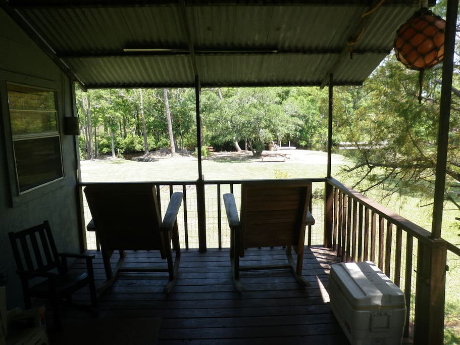 Rocking chairs on the covered porch with a view of Bayou Jonas in the backyard.