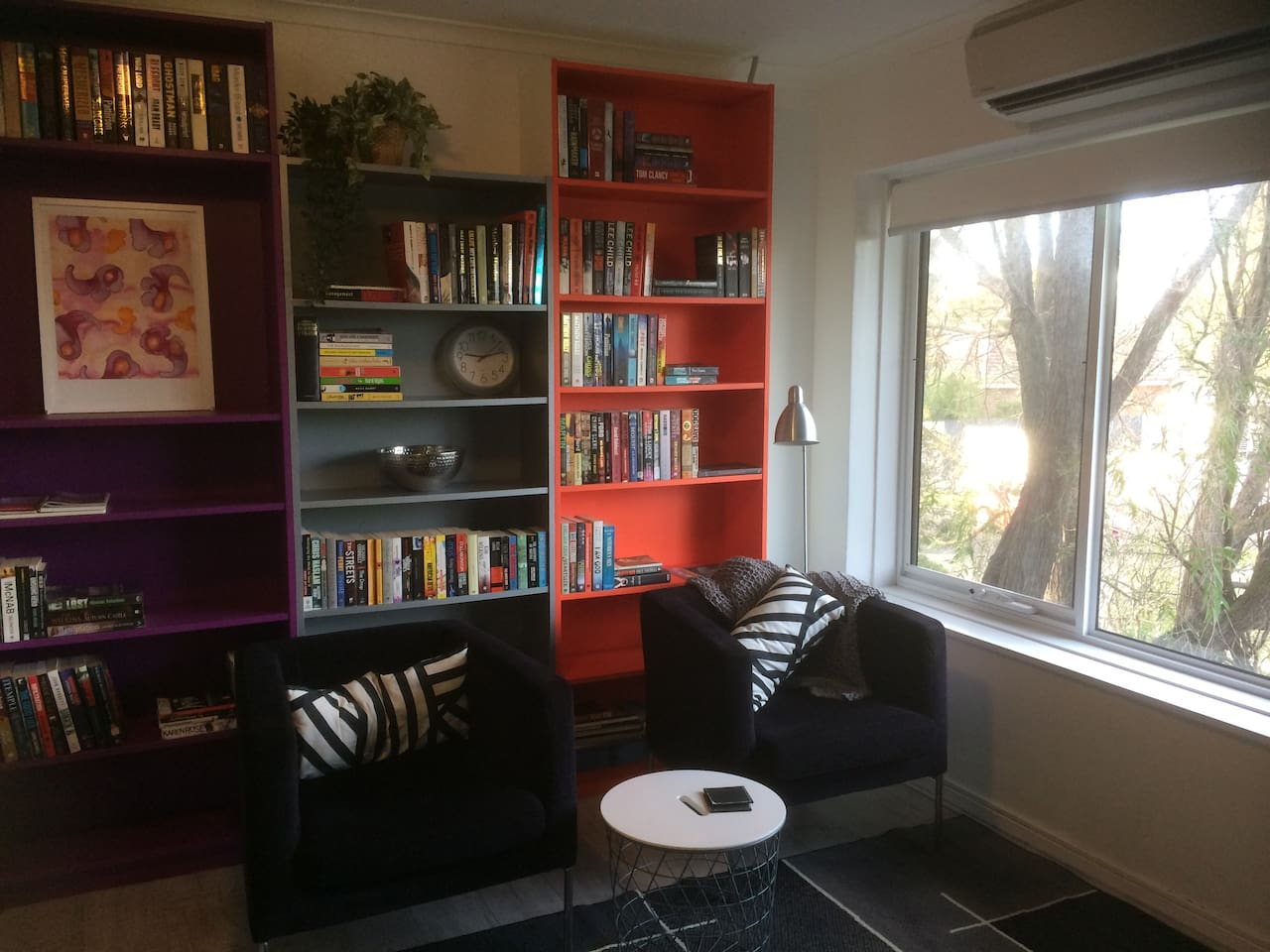 Leafy outlook to street. Wall mounted TV, 2 comfortable black-purple velvet chairs and a large selection of books for our guests to read. This area forms part of the kitchen, dining and living.