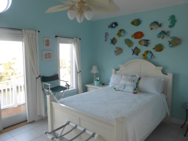 Upstairs guest bedroom - queen bed attached balcony overlooking boat dock and evening sunsets.