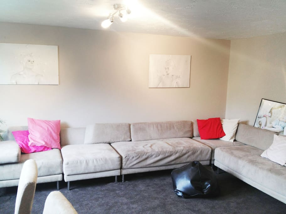 The living room with a beautiful suede habitat sofa.  Why not invite your friends around for a drink? You can fit 10 of them easily on the sofa. 1 can sit on the bean bag.