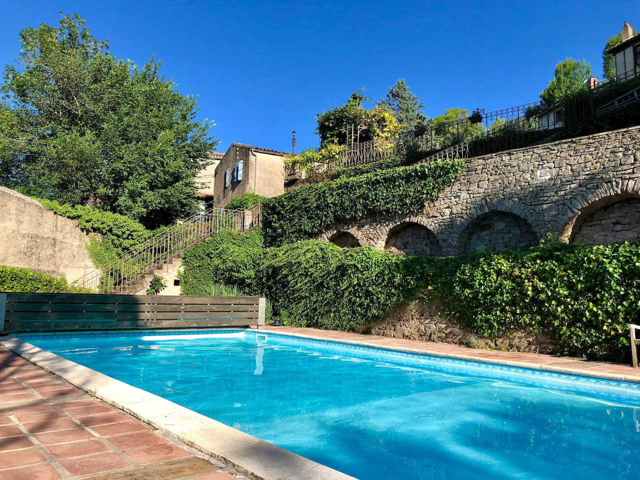 View of the pool looking to the terrace above and the Gite on the left hand side with the blue shutters