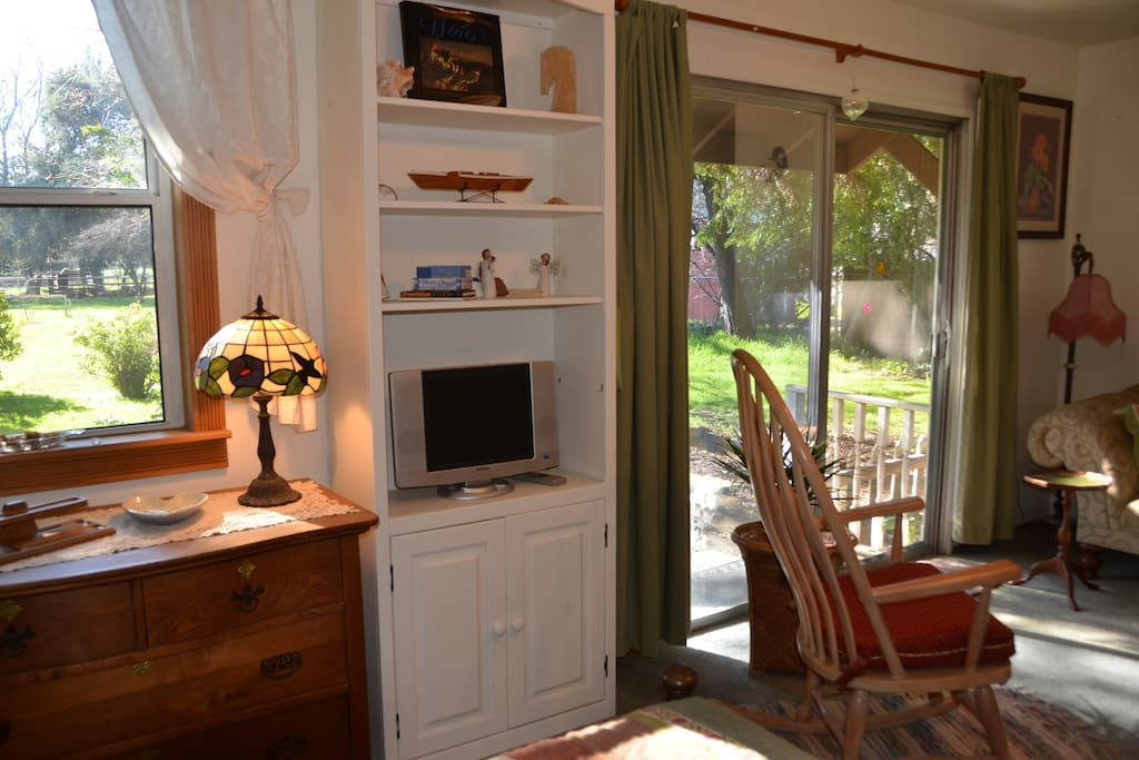Front window & sliding door views, dresser, TV w/HD antenna, comfortable rocker