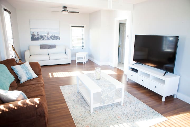 """Spacious living room with 65"""" Smart TV."""
