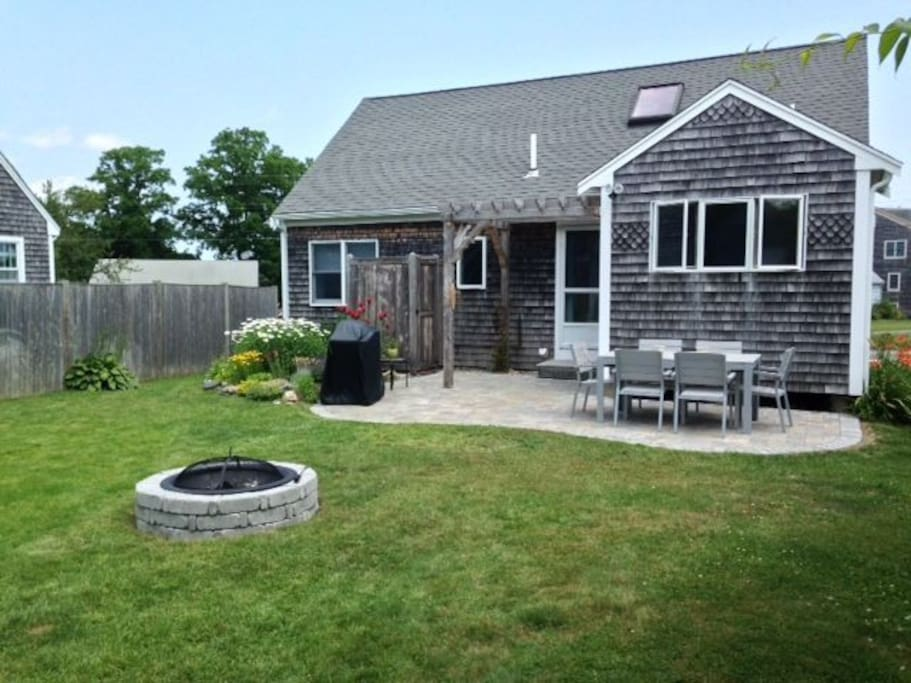 Back of cottage with fire pit, grill, outdoor shower and outdoor seating