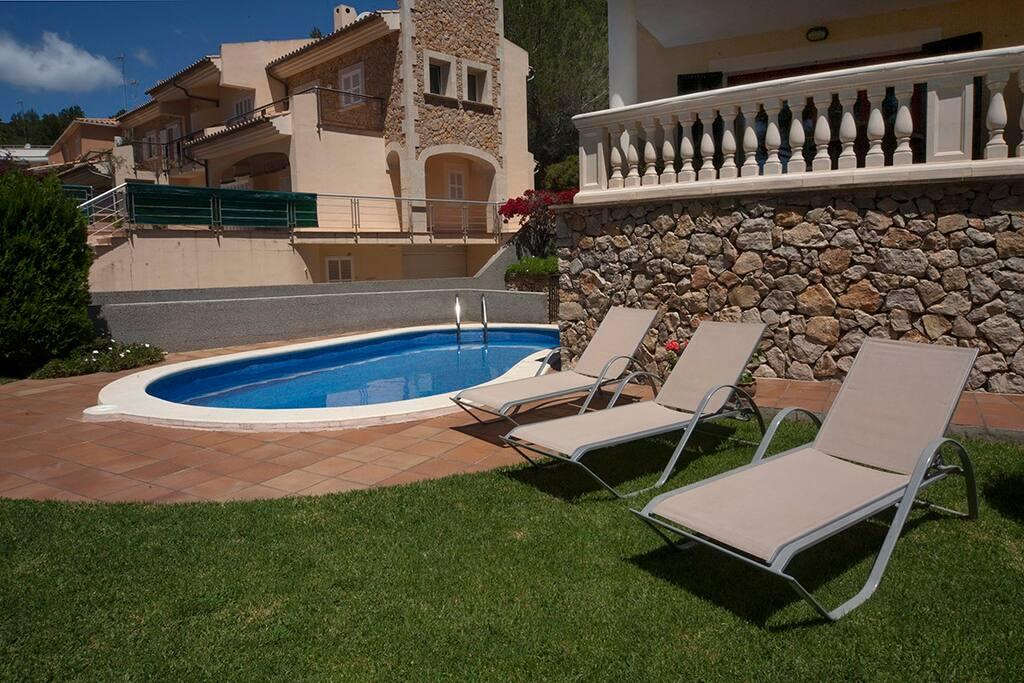 vista detalle de las tumbonas, la piscina y el jardín