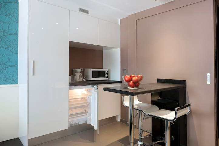 Small kitchen space with a fridge, microwaves, coffee machine and a kettle.