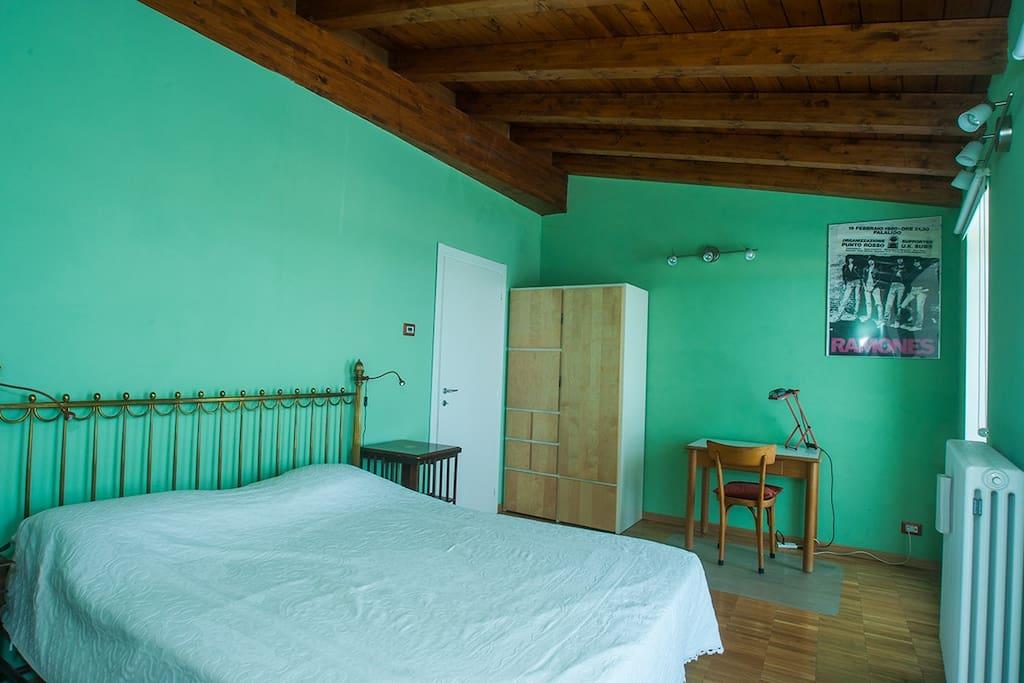 Camera verde con il letto matrimoniale
