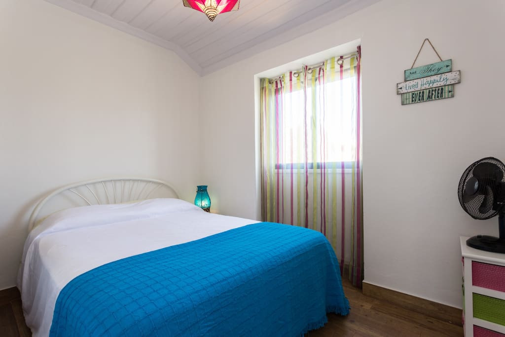 Blue room with standard double bed.