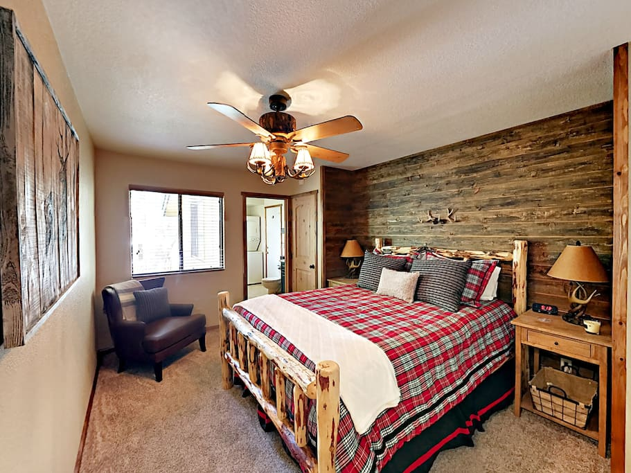 The second bedroom is furnished with a queen bed, armchair, and natural wood accents.