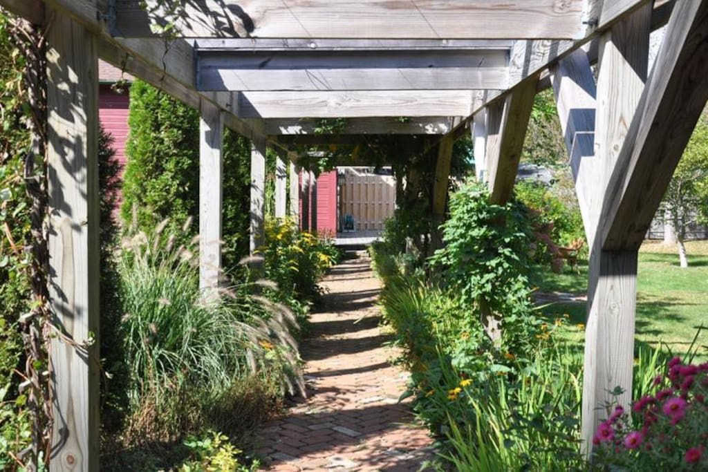 60 foot Pergonal with mature wisteria and perennial gardens on either side.