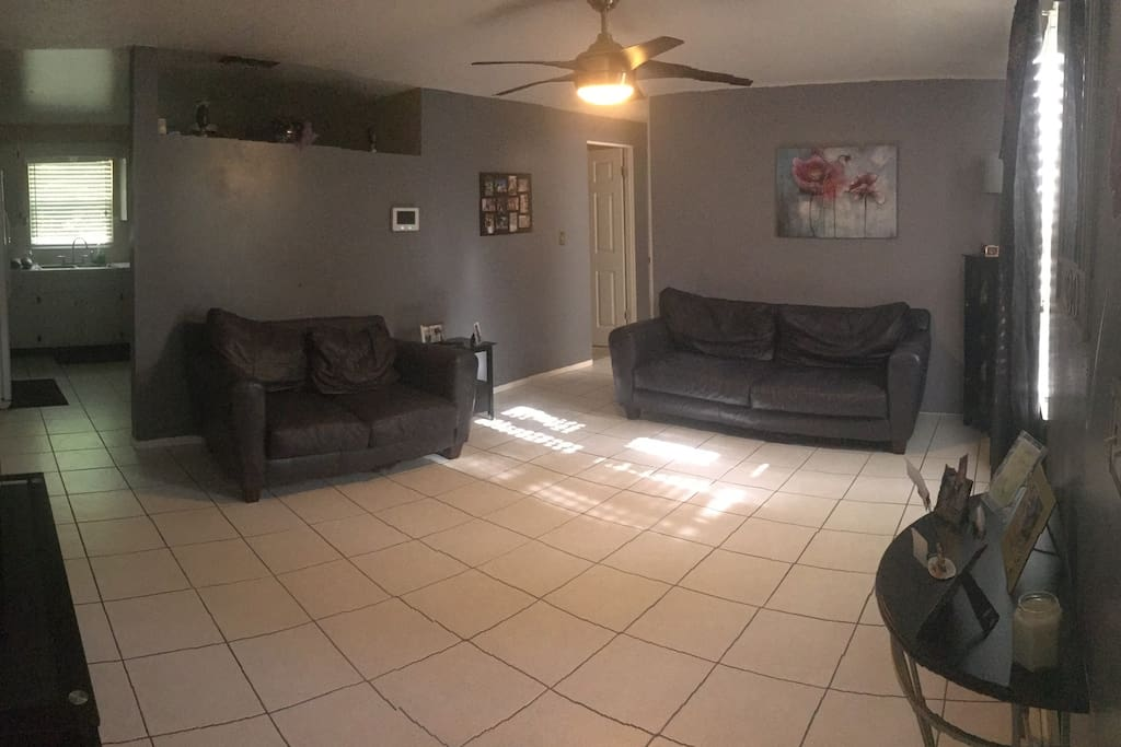 Shared living room with sofa, love seat, and TV.