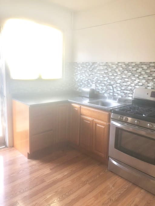 full kitchen with gas stove, refrigerator, toaster, coffee maker