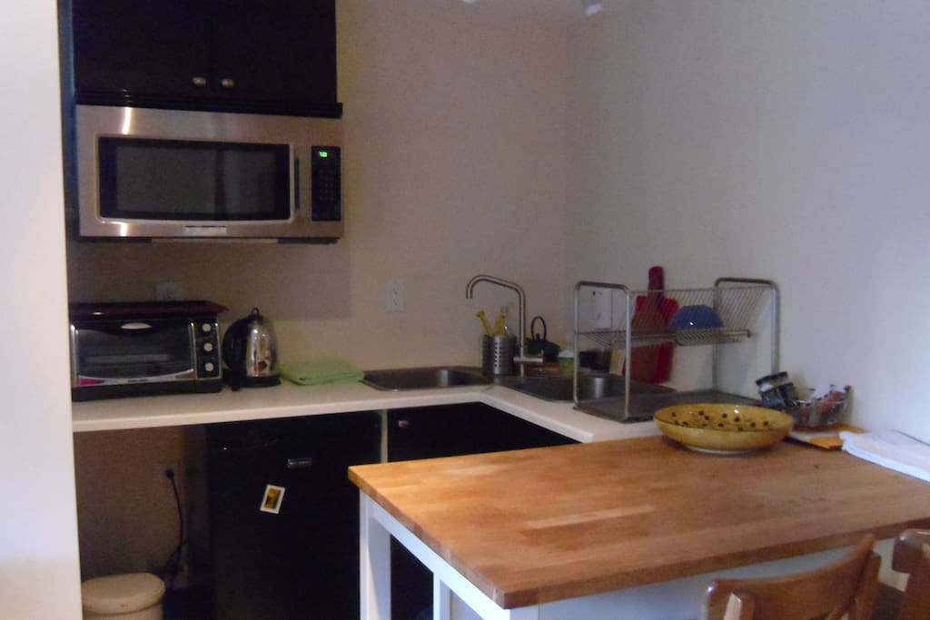 Kitchenette with table, 2 stools, under counter fridge, sink, toaster oven, microwave, portable stove top