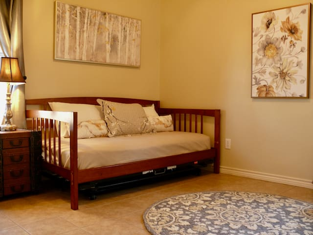 Bedroom with a day bed, trundle, and window seating.
