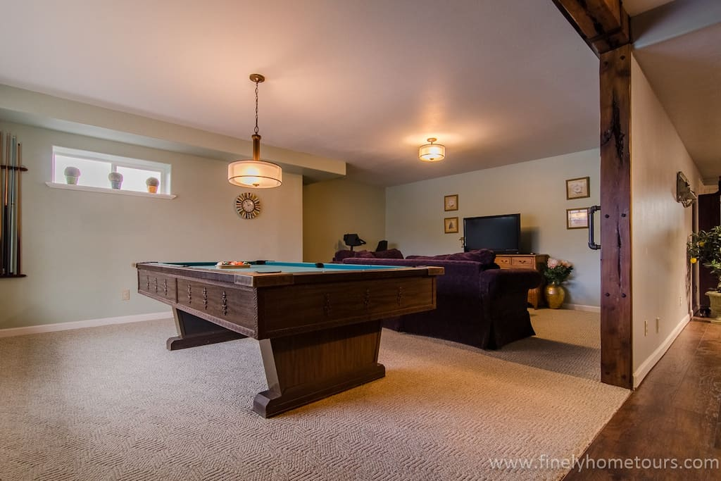 The large entertainment area includes a pool table, TV, comfy couch in a large carpeted space.