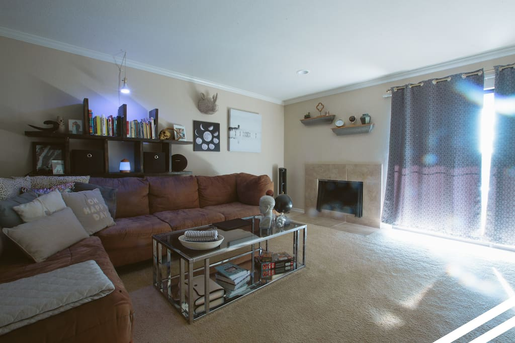 Living room with fireplace and access to patio. TV (not pictured) with cable TV available.