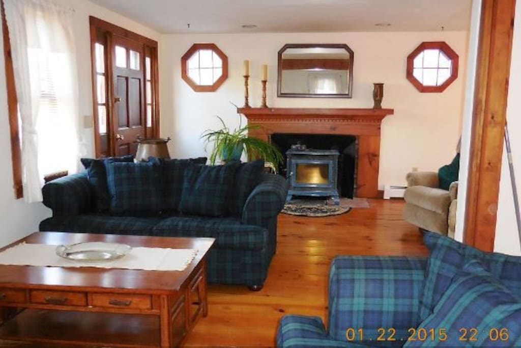 Living area with fireplace, two love seats and hardwood floors