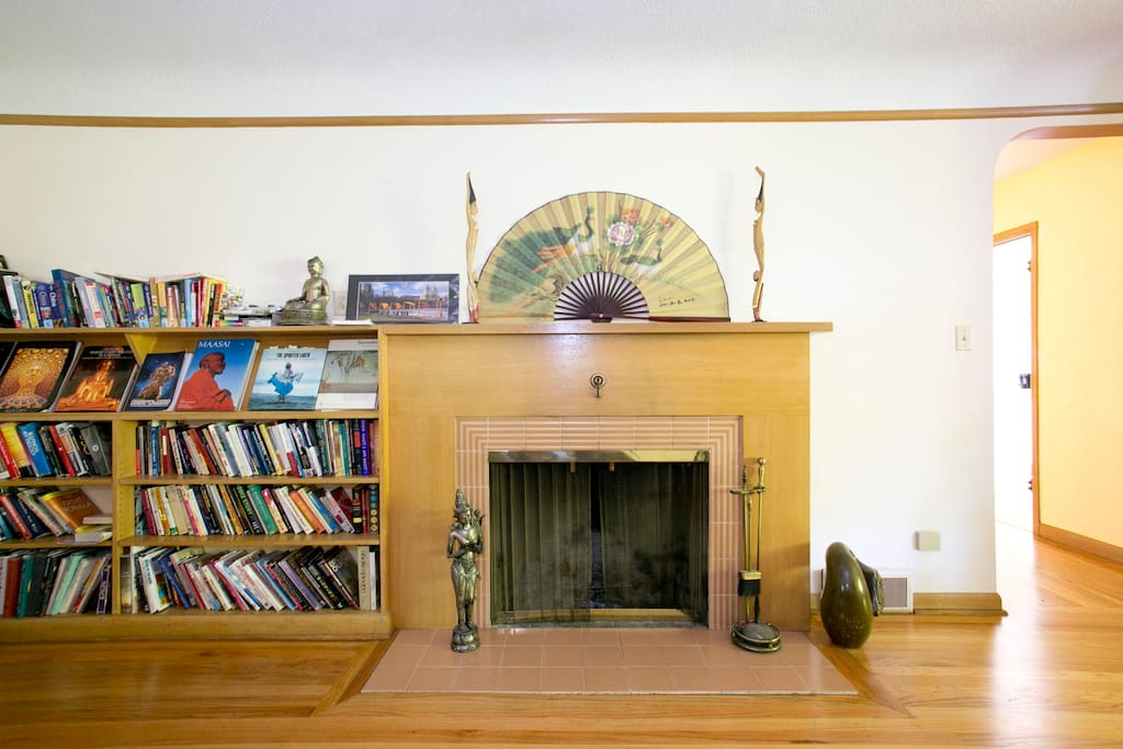A frontal view of the  fireplace and library of self help, health and fitness, psychology, and travel books.