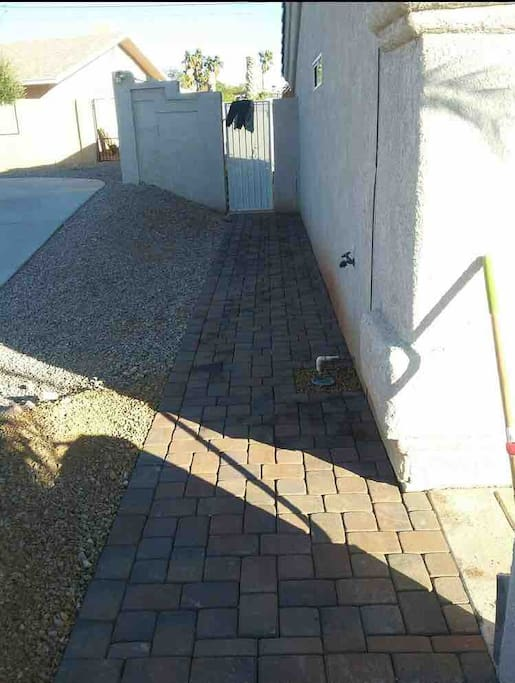 Left side of house, paved walkway to side entry gate. Latch is on top(inside gate)