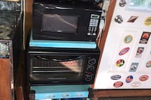 Two burners, microwave, small oven, pots, pans, baking pans;